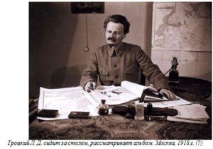 Троцкий Л. Д. сидит за столом, рассматривает альбом. Москва, 1918 г. (?)